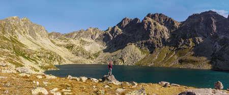 Mountain lake in the Tatras. A woman standing by the lake. Mountain tourism.