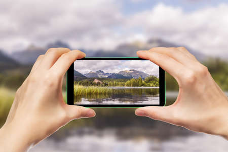 Hands holding a mobile phone. Photographing mountain landscapes using a smartphone. Standard-Bild