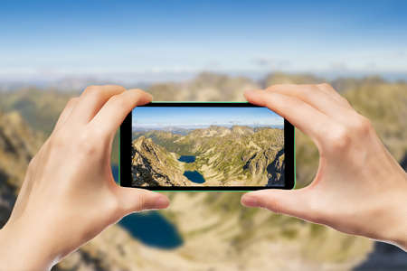 Photographing mountain landscapes using a smartphone. Hands holding a mobile phone. Standard-Bild