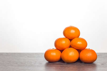 Mandarins lying on counter. Pyramid composed of mandarins. Citrus fruit on a white background. Stockfoto