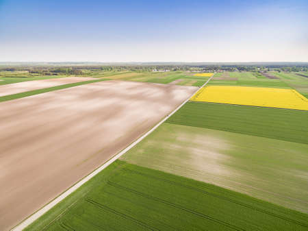Rural landscape from a bird's eye view. Road through a cultivated field. Poland - rural areas from the air.