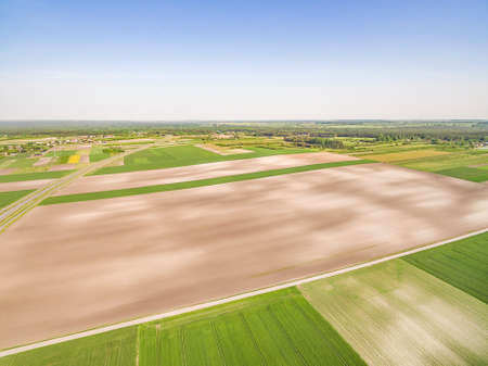 Agricultural landscape from a bird's eye view. Poland - rural areas from the air. Cultivated fields stretching to the horizon.