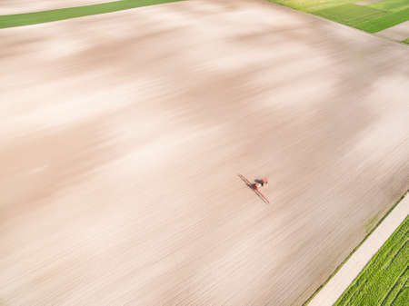 Agricultural landscape seen from the bird's eye view. Agricultural tractor working on the field. Standard-Bild
