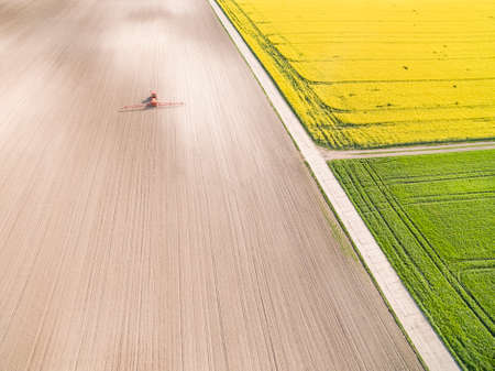 Agricultural landscape seen from the air. Agricultural tractor working on the field. Farmland from a bird's eye view.