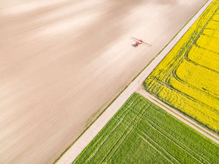 Landscape of cultivated fields from a bird's eye view. Agricultural tractor working on the field.