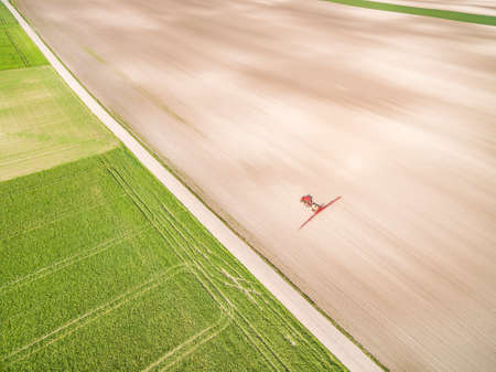 Agricultural tractor working in spring on a farmland. Agricultural landscape from a bird's eye view. Standard-Bild
