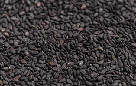 Background from grains of black sesame seeds. Mosaic from grains of cereal transition into soft focus.