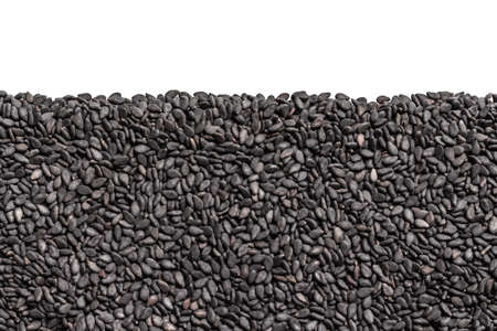 Grains of black sesame seeds. Background with seeds with empty space on top. Seamless texture with black seeds.