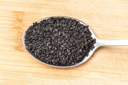 Grains of black sesame on a wooden chopping board. Additives to eat - sesame seeds. Healthy food. Food background.