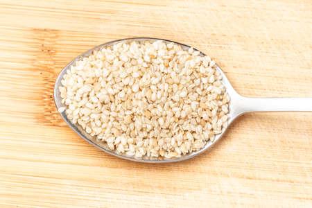 Sesame seeds on a wooden spoon lying on a wooden chopping board. Standard-Bild