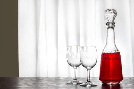 A carafe with wine and two glasses. Drawn curtains in the window. A romantic meeting by the wine.