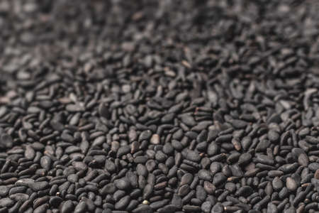 Black sesame seeds. Background from black beans turning into soft focus. Additives to eat - sesame seeds. Healthy food. Standard-Bild