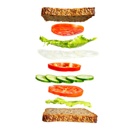 Sandwich with vegetables. Vegetarian sandwich with rye bread, lettuce, tomatoes and cucumbers. Vegetable ingredients, floating in the air.