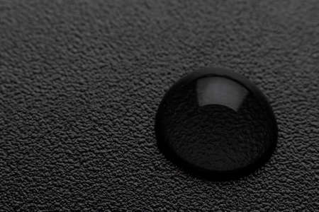 Water drop on a black background. Black background texture out of focus in blur and a drop of water. Standard-Bild