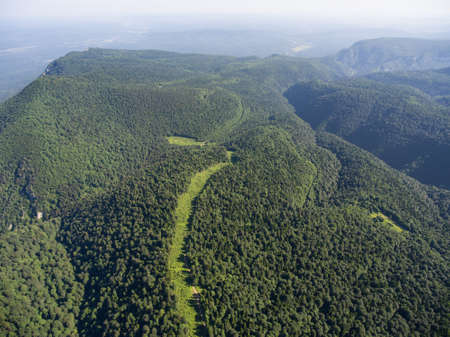 foliar: Aerial photos. The mountain ridge covered forest. The road in the forest. Mountain landscape. Caucasus.
