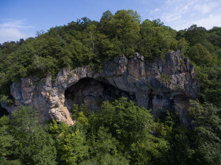 cave exploring: Aerial Photos. The cave entrance is emblazoned on the side of a mountain covered with forest.