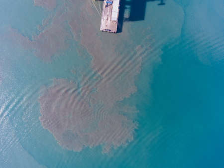 defilement: Aerial view of the dirt in the water near the pier at the port. Stock Photo