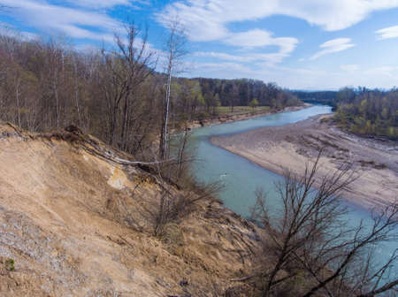 Bend in the river and clay crumbling shore with trees. Drone photo.