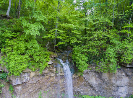 Long the flow of the waterfall cascading from the cliff. Aerial view. Drone photo.