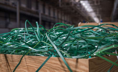 The pile of waste plastic strip in wooden box. Stock Photo