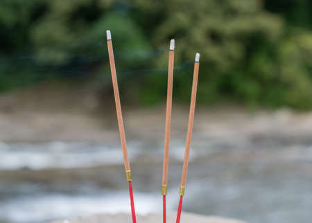 Three buddhist burning incense sticks on a river. Selective focus. Stock Photo
