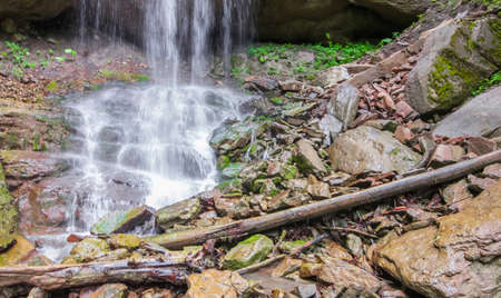 Large boulders and logs at the foot of the waterfall. Selective focus. Stock Photo