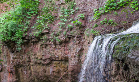 The stream flowing down from the red cliff. Selective focus. Stock Photo