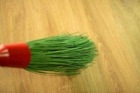 Long green plastic broom. Selective focus.