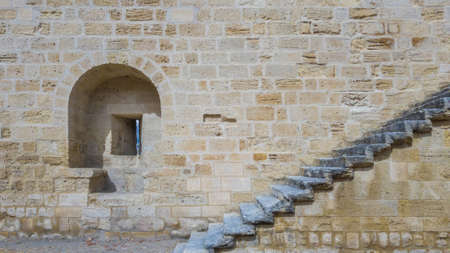An embrasure and a staircase on the stone wall of an ancient fortress. Stock Photo