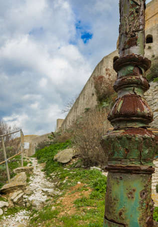 Old metal lantern with peeling green paint. A tourist trail near the walls of a stone fortress. Stock Photo