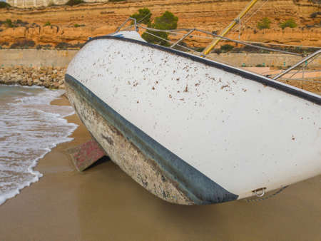 The hull of a sailboat thrown by a storm on the shore of the sea.
