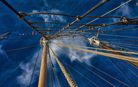 Wooden masts and rigging of a sailing vessel. Stock Photo