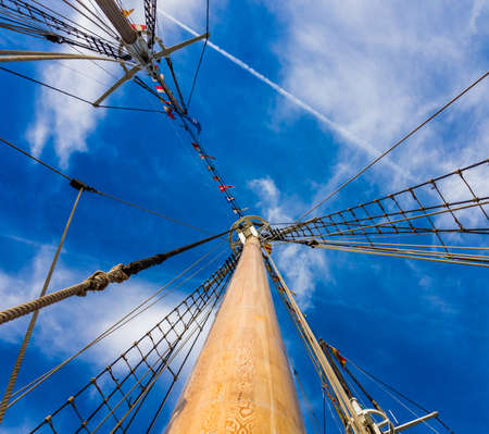 Masts and rigging of a sailing ship against the blue sky background. Stock Photo