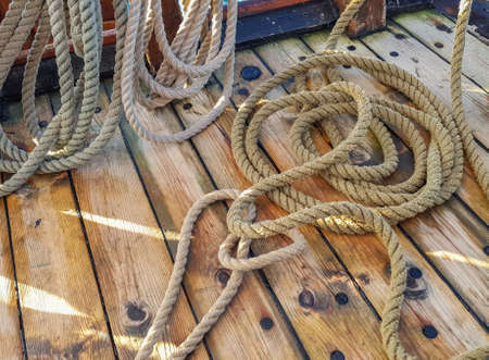 Thick old ropes on the wooden deck of the ship.
