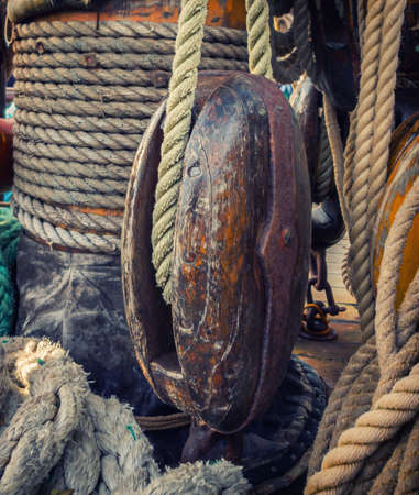 Wooden block and ropes on the background of the mast of the sailing ship.