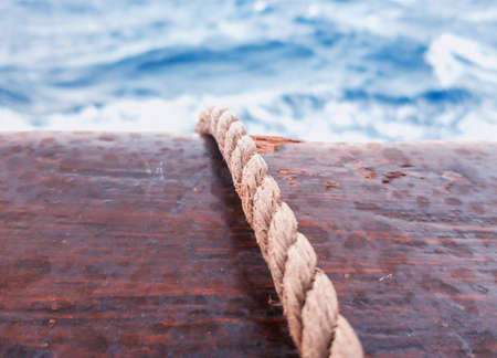A rope slung across the wooden side of the ship. Selective focus.