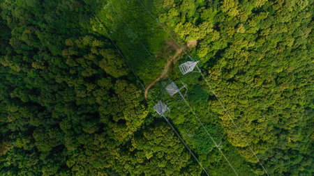 Aerial view. High voltage metal post. High-voltage towers in the forest. Top view.