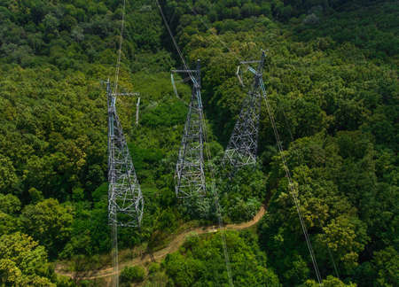 Aerial view. High voltage metal post. High-voltage towers in the forest.