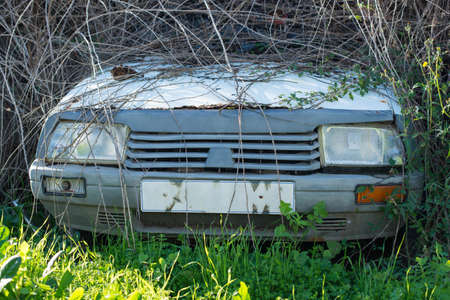 Abandoned old white sedan in a junkyard. Front view. 版權商用圖片 - 136008627