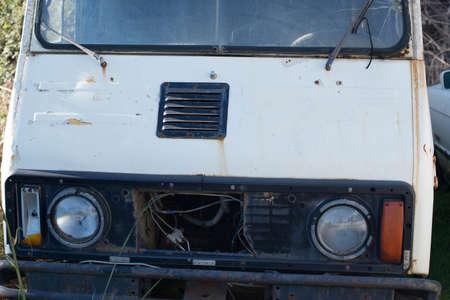 Abandoned old white minivan in a junkyard. 版權商用圖片 - 136008539