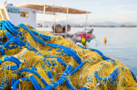 A yellow-and-blue fishing net is piled near a fishing boat. 版權商用圖片