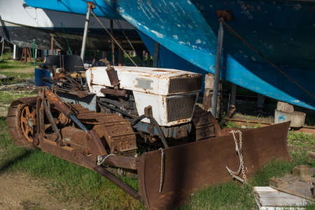 A small old abandoned bulldozer is rusting in a yacht yard.