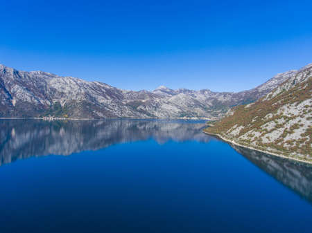 Beautiful fjord of Montenegro. Calm in the Bay of Kotor. Reflection of mountains on water. Aerial view.