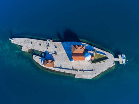 An artificial island in Montenegro with a tourist yacht moored. Top view.