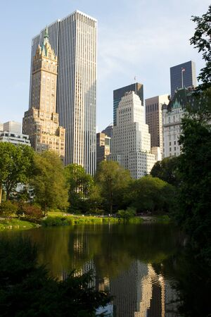 People relaxing by the small lake on a sunny Summers day at south Central Park, Manhattan, New York