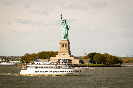 Boats of tourists going to Liberty Island to see the Statue of Liberty on the East and Hudson Rivers in lower Manhattan, New York. Stock Photo
