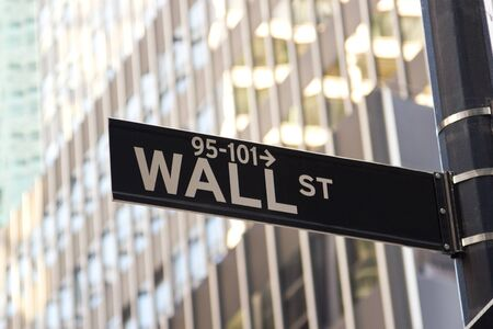 The street sign of Wall Street with an office building behind it.