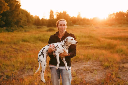 Happy man holding a big spotted dalmatian dog in hands, smiling and looking at camera. Yellow grass and sunset on the background.