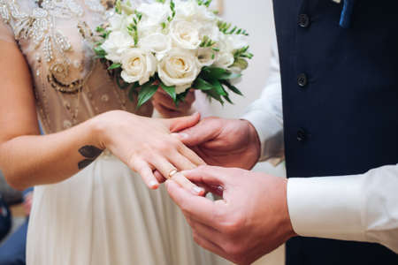 fingers put together: Croped Bride and groom with wedding rings at ceremony exchange