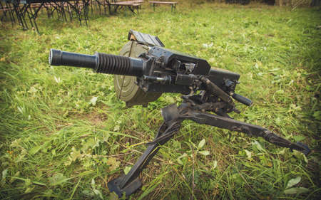 Front view at grenade launcher weapon against tanks lying on ground.